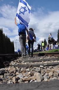 041  Students Carry Israeli Flag walking along the train tracks leading to Auschwitz Birkenau