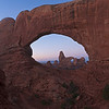 This image was shot on a relatively cool morning in the middle of January.  While there was some snow on the ground, it wasn't an issue climbing to the perch that's located just across from the North Window here in Arches National park.  <br /> <br /> On this day as I was making a duplicate of the classic of Turret Arch through the North Window, a fog arrived from the east that eventually obscured the area.  The beginnings are just being seen to the left of this image. <br /> <br /> I retreated from this perch to avoid being caught in the fog with potentially slippery freezing moisture conditions.<br /> <br /> One thing I figured out after making the strenuous climb up to the perch here is my down jacket is extremely susceptible being degraded by sweat.  I sweated like I normally do which was absorbed by my jacket.  Eventually that cause the down to lose much of its heat retention capabilities.  As awesome as down is for retaining heat, it's very susceptible to me and my ability to sweat through anything.