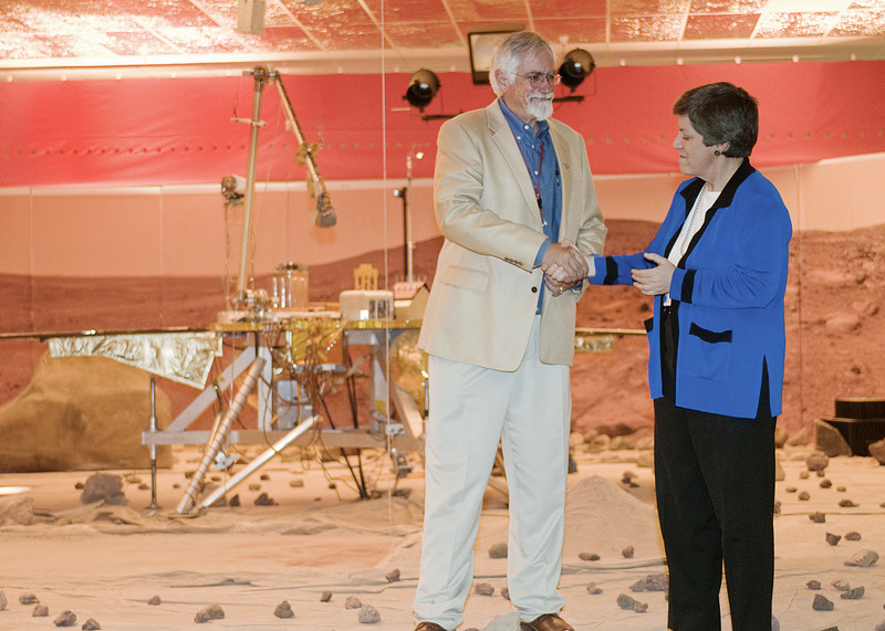 (2.13.2008 -- Tucson, AZ)  Arizona Governor Janet Napolitano shakes hands with Dr. Peter Smith, Principal Investigator of the Phoenix Mars Mission in front of a model of the lander.