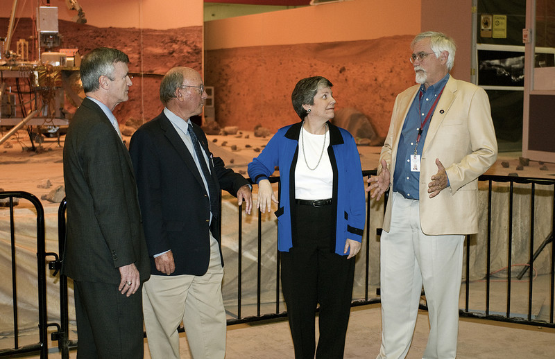 (2.13.2008 -- Tucson, AZ)  University of Arizona President Robert Shelton (left) and Dr. Michael Drake look on as Phoenix Mars Mission Director Peter Smith briefs Arizona Governor Janet Napolitano as they stand in front of a model of the lander.