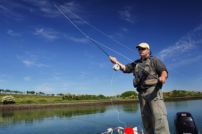 Angler casting from boat with fly rod on Strangford Lough for seatrout
