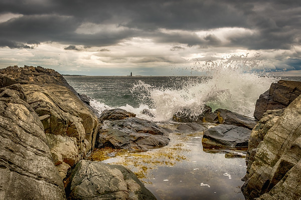 Waves crash along the coast near Portland, Maine on August 18, 2018. Historic Ram Island Ledge Light Station can be seen on the horizon.