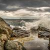 Waves crash along the coast near Portland, Maine on August 18, 2018. Historic Ram Island Ledge Light Station can be seen on the horizon.