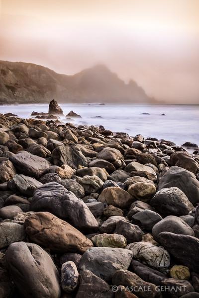 Pastel fog on rocky shore