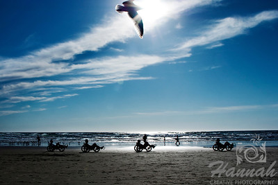 View of the beach with silhouette of people riding their tricycles and a bird in flight.  Backlighting shot at Cannon Beach, Oregon Coast.  © Copyright Hannah Pastrana Prieto
