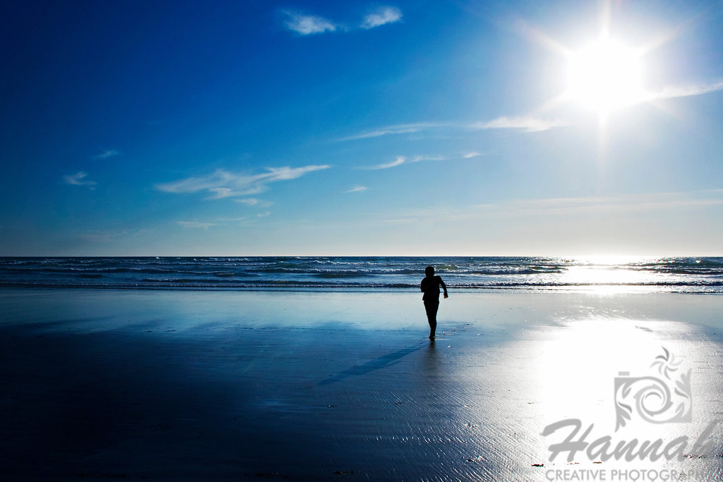 View of the beach with a silhouette of a boy running.   Backlighting shot at Cannon Beach, Oregon Coast.  © Copyright Hannah Pastrana Prieto