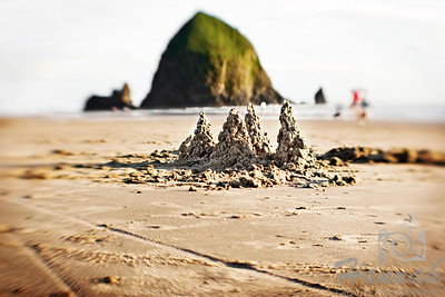 A sandcastle with a view of Haystack Rock at Cannon Beach in Oregon Coast. Shot with the Lensbaby composer.  © Copyright Hannah Pastrana Prieto