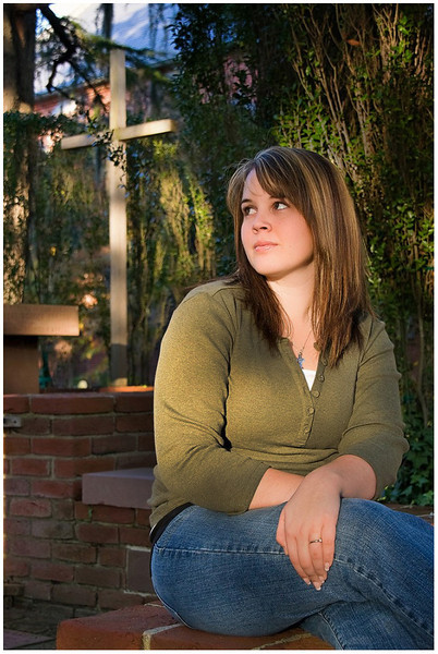 Professional lifestyle portrait of a senior in downtown New Bern, NC at Christ Church with a cross in the background.