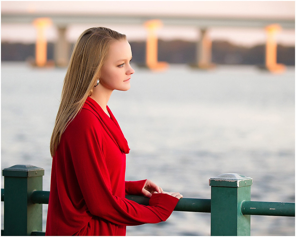 Professional portrait of a senior at Union Point Park New Bern, NC looking out over the Neuse river with the bridge in the background.