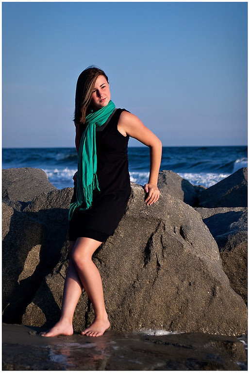 Professional portrait of a senior at Fort Macon Beach State Park North Carolina standing by rocks at the beach.