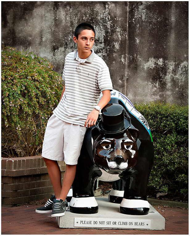Professional portrait of a senior in downtown New Bern, NC leaning on a bear.