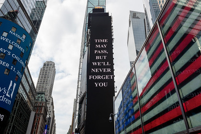 "NEW YORK, NEW YORK - SEPTEMBER 11: A ""time may pass, but we'll never forget you"" sign is displayed on One Times Square near a large American Flag in Times Square as the city continues Phase 4 of re-opening following restrictions imposed to slow the spread of coronavirus on September 11, 2020 in New York City. The fourth phase allows outdoor arts and entertainment, sporting events without fans and media production. (Photo by Alexi Rosenfeld/Getty Images)"