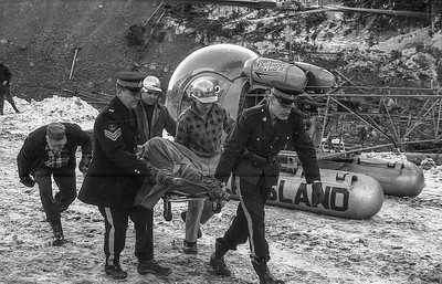 RCMP and rescue workers carry the body of a tanker truck driver killed in Canada's largest-ever landslide east of Hope, BC, on the morning of Jan. 9, 1965. Three other motorists also lost their lives in the disaster and two of their bodies were never recovered. (CP Wirephoto)1965(Wally Hayes)