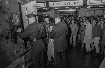 Curious onlookers watch Vancouver police arrest a man during riots preceding the playing of the 54th Grey Cup in November 1966. The Grey Cup is to Canadian Football what the Super Bowl is in the United States. (CP Wirephoto)1966(Wally Hayes)