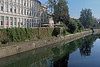 Mid-morning reflections upon the Ljubljanica River - viewing eastward along the Petkovskovo embankment, to the distal Mesarski Most (Butcher's Bridge) - Ljubljana city.