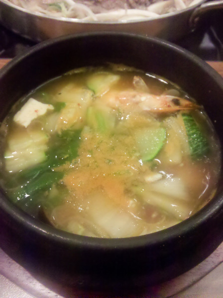 Soup with some seafood and stuff inside.