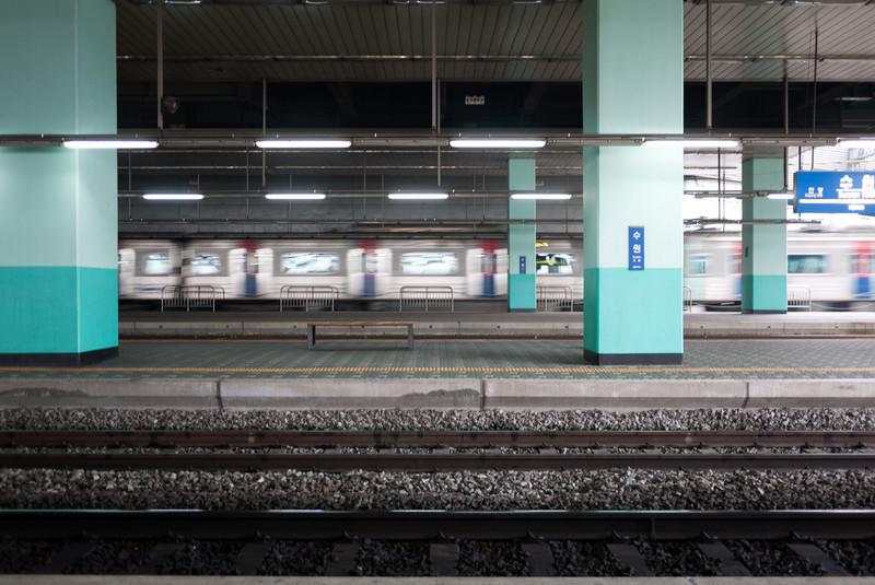 A subway train passing through Suwon Station.