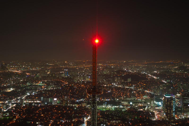 Night view from the observation deck atop the N Seoul Tower facing the adjacent transmission tower.