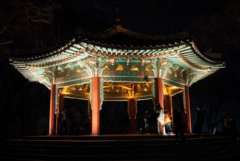 Octagonal pavilion next to N Seoul Tower at night.