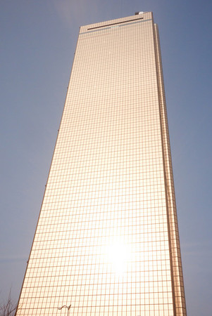 The reflection of the sun is visible and extremely bright against the side of the 63 City building.