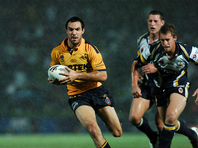 01 SEP 2006 TOWNSVILLE, QLD - Parramatta fullback Wade McKinnon is chased by Clint Amos during a downpour - North Queensland Cowboys v Parramatta Eels (Dairy Farmers Stadium) - PHOTO: CAMERON LAIRD