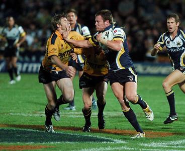 01 SEP 2006 TOWNSVILLE, QLD - Gavin Cooper fends of Parramatta's Glenn Morrison - North Queensland Cowboys v Parramatta Eels (Dairy Farmers Stadium) - PHOTO: CAMERON LAIRD