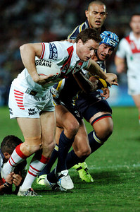 05 AUG 2005 TOWNSVILLE, QLD - Johnathan Thurston reaches out to try and bring down Colin Best - (North Queensland Cowboys v St George Illawarra Dragons, Dairy Farmers Stadium, Townsville) - PHOTO: CAMERON LAIRD