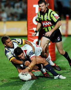 05 AUG 2005 TOWNSVILLE, QLD - Trent Barrett scores in the second half despite the best efforts of Cowboys fullback Matt Bowen - (North Queensland Cowboys v St George Illawarra Dragons, Dairy Farmers Stadium, Townsville) - PHOTO: CAMERON LAIRD
