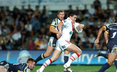 05 AUG 2005 TOWNSVILLE, QLD - Clint Greenshields escapes the grasp of Steve Southern - (North Queensland Cowboys v St George Illawarra Dragons, Dairy Farmers Stadium, Townsville) - PHOTO: CAMERON LAIRD