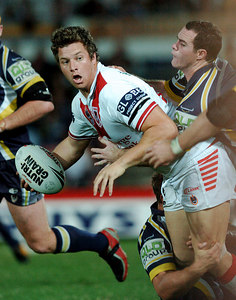 05 AUG 2005 TOWNSVILLE, QLD - Brett Firmin tries to bring down Ashton Sims - (North Queensland Cowboys v St George Illawarra Dragons, Dairy Farmers Stadium, Townsville) - PHOTO: CAMERON LAIRD