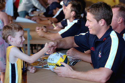 21-SEP-2004  TOWNSVILLE, QLD - Cowboy five-eighth David Myles with Jake Riley, 6 at a public autograph session - PHOTO: CAMERON LAIRD