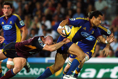 12 MAY 2006 TOWNSVILLE, QLD - David Croft tries to drag down Seilala Mapusua  during the Queensland Reds 22-16 win over the Highlanders in their Super 14 clash at Dairy Farmers Stadium, Townsville - PHOTO: CAMERON LAIRD