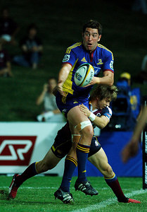 12 MAY 2006 TOWNSVILLE, QLD - Drew Mitchell takes Hoani MacDonald over the sideline during the Queensland Reds Super 14 match against the Highlanders at Dairy Farmers Stadium, Townsville - PHOTO: CAMERON LAIRD
