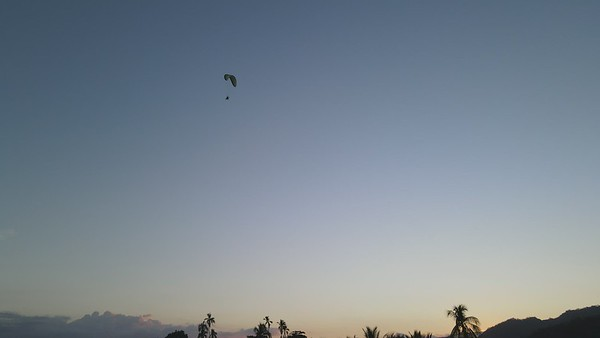 Paragliding at the beach at sunset
