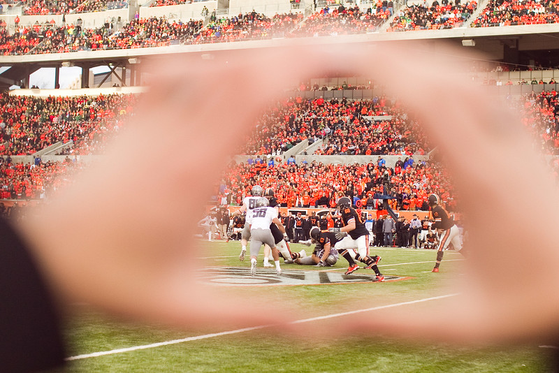 """Viewpoint through the Oregon hand """"O""""  of Oregon State Beavers quarterback Ryan Katz (12) making a pass at the 114th annual Civil War. UO Defeated OSU 37-20 in the game at Reser Stadium in Corvallis Oregon."""