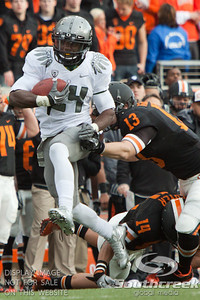 U of O RB Kenjon Barner (24) tries to escape the tackle of Oregon State  LB Rueben Robinson (13) during the 2010 Civil War game at Reser Stadium, Corvallis, Oregon.  The Oregon Ducks beat the Oregon State beavers 40-20.