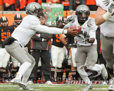 Oregon QB Darron Thomas (1) hands the ball off to RB Kenjon Barner (24) during the 2010 Civil War game at Reser Stadium, Corvallis, Oregon.  The Oregon Ducks defeated the Oregon State Beavers 37-20 to advance to the BCS National Championship game in Glendale, Arizona.