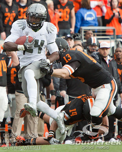 Oregon RB Kenjon Barner (24) outruns the attempted tackles of Oregon State LB Rueben Robinson (13) and CB Jordan Poyer (14) during the 2010 Civil War game at Reser Stadium, Corvallis, Oregon.  The Oregon Ducks defeated the Oregon State Beavers 37-20 to advance to the BCS National Championship game in Glendale, Arizona.