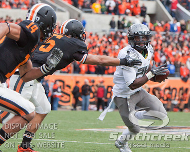 Oregon LB Cameron Collins (5) reaches out to tackle Oregon outruns the attempted tackle of Oregon RB Kenjon Barner (24) with the help of CB Jordan Poyer (14) during the 2010 Civil War game at Reser Stadium, Corvallis, Oregon.  The Oregon Ducks defeated the Oregon State Beavers 37-20 to advance to the BCS National Championship game in Glendale, Arizona.