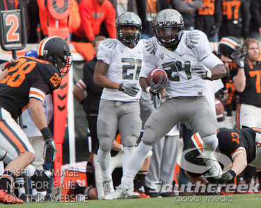 Oregon RB Kenjon Barner (24) outruns Oregon State LB Rueben Robinson (13) but faces Oregon State S Suaesi Tuimaunei (28) during the 4th quarter of the 2010 Civil War game at Reser Stadium, Corvallis, Oregon.  The Oregon Ducks defeated the Oregon State Beavers 37-20 to advance to the BCS National Championship game in Glendale, Arizona.