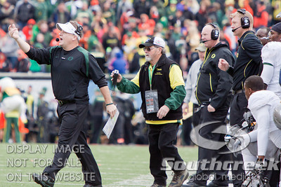Oregon coach Chip Kelly (left) charges onto the field to get the attention of his players during the 3rd quarter of the 2010 Civil War game at Reser Stadium, Corvallis, Oregon.  The Oregon Ducks defeated the Oregon State Beavers 37-20 to advance to the BCS National Championship game in Glendale, Arizona.