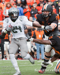 Oregon RB Kenjon Barner (24) attempts to elide the tackles of Oregon State DT Kevin Frahm (74) and LB Dwight Roberson (59) during the 2010 Civil War game at Reser Stadium, Corvallis, Oregon.  The Oregon Ducks defeated the Oregon State Beavers 37-20 to advance to the BCS National Championship  game in Glendale, Arizona.