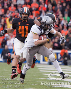 Oregon State CB James Dockery (4) horse-collars Oregon WR Jeff Maehl (23) while LB Feti Unga (41) chases during the 4th quarter of the 2010 Civil War game at Reser Stadium, Corvallis, Oregon.  The Oregon Ducks defeated the Oregon State Beavers 37-20 to advance to the BCS National Championship game in Glendale, Arizona.