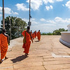 Visiting monks walk around the base of the large dagoba at Mihintale.
