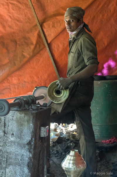 A man polishing brass with a machine in an outdoor tent at another place.