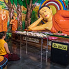 The prayer room and reclining Buddha at the dagoba. A visiting monk kneels on the floor to the left. This was the most colourful room with Buddha that we saw, decorated on all sides.