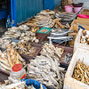 Dried fish market stalls next to the beach drying area.