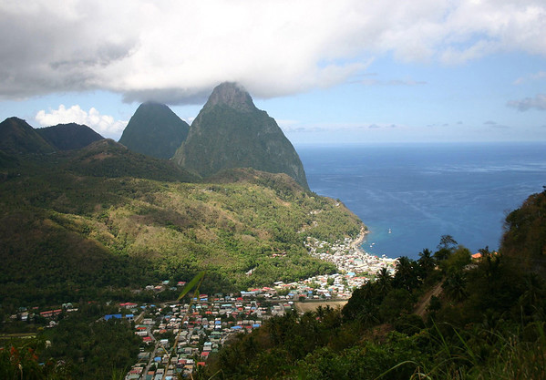 Soufrière Bay and town - Piton Mitan Ridge - and the cloud covered summits of Petit Piton, rising to 2,438 ft. (743 m) and beyond to Gross Piton, whose peak touches 2,525 ft. (770 m) - all part of the Quailbou Depression, a collapsed strata (composite) volcano, measuring about 4.3 mi. (7 km) from here along the slopes at Mt. Malmaiso to the distal Gross Piton