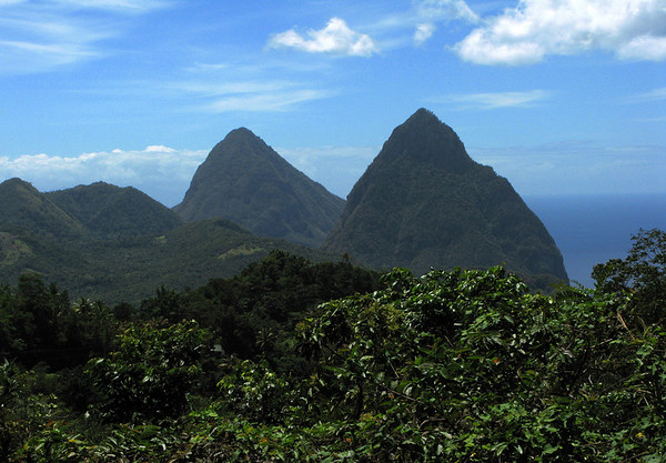 """Beyond the tropical forest along the Piton Mitan Ridge - over to the pyramidal lava domes of Petit Piton (foreground) which is about 88 ft. (27 m) lower - the Gros Piton, which is about 1.5 mi. (2.4 km) southward, from summit to summit - all three part of the """"Pitons Management Area"""" which is was designated in 2004, as a UNESCO World Heritage Site"""