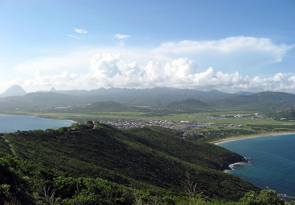 Along the vegetated slope of the isthmus of the whale's fluke-shaped peninsula, Cape Moule à Chique (the southern most end of the island) - with Vieux Fort Bay (L) and Anse des Sables Bay (R, Sandy Beach Bay) - with the peaks of the Twin Pitons seen along the L. horizon